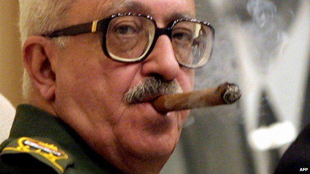 Tariq Aziz smokes a cigar during a meeting in Baghdad, Iraq - 18 September 2002