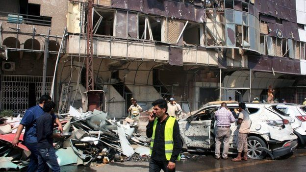 Iraqis gather at the scene of a car bomb attack at Kahramana Square in the Karada district of central Baghdad