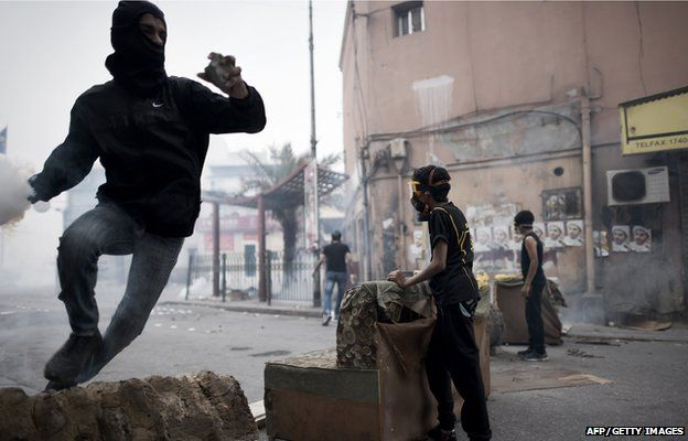 A Bahraini protester prepares to throw back a tear gas canister during clashes with police following a demonstration on February 13, 2015