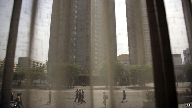 People walk down a street past a restaurant and apartment buildings, Wednesday, May 6, 2015, as photographed through the curtained window of the Koryo Hotel in central Pyongyang, North Korea.