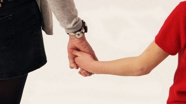 boy and adult hold hands