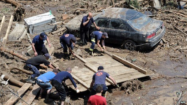 Rescuers and local residents collect debris at a flooded area in the Georgian capital Tbilisi on 15 June 2015.