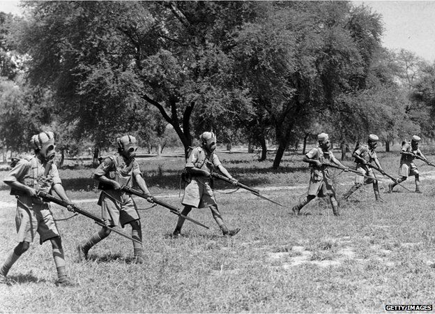 circa 1940: Indian infantrymen wearing gas masks over their turbans during exercises in preparation for duty in the Second World War.