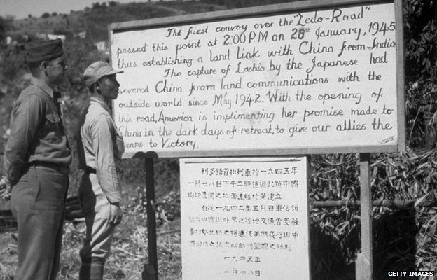 An American and a Chinese soldier reading a sign detailing the first convoy over the Ledo Burma Road, linking China with India.