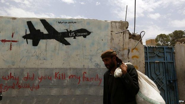 A man walks past graffiti condemning the US drone campaign in Yemen (16 June 2015)