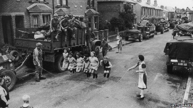 A US soldier helps British children with their skipping