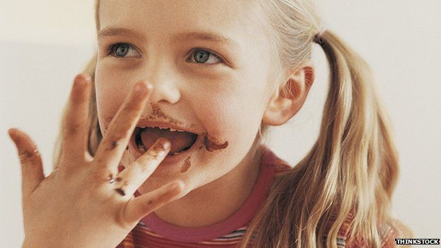A girl licking her fingers, which are covered with chocolate