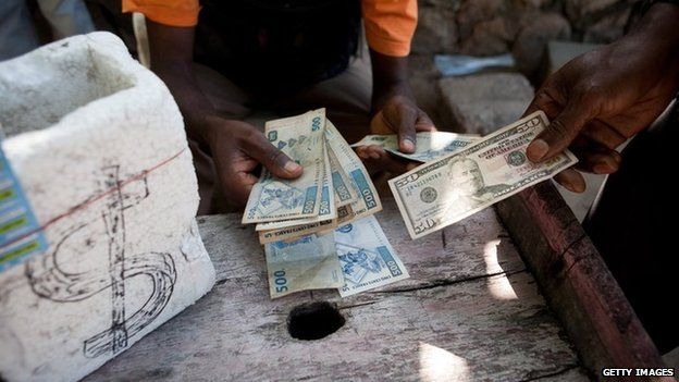 A man changes a 50 USD bank note for Congolese Francs with a money changer in the street of Kinshasa.