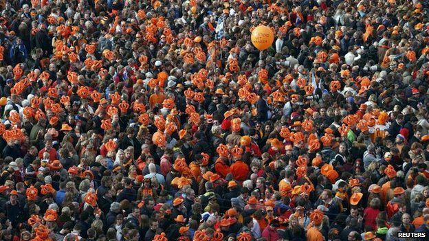 An orange balloon is seen above the crowd gathered for Queen Beatrix's abdication ceremony in Amsterdam.