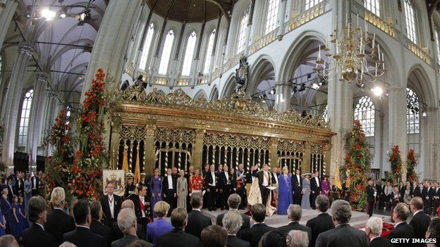 HM King Willem-Alexander of the Netherlands and his wife HRH Princess Beatrix of the Netherlands stand with members of the royal household during their inauguration ceremony at Amsterdam's New Church, 30 April 2013