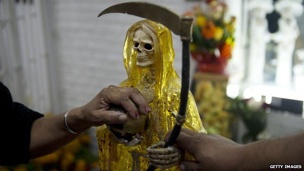 Devotees touch the figure of Santa Muerte at an altar in Mexico City on 1 November, 2012