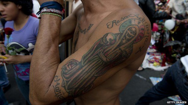 A man with a tattoo of Santa Muerte attends a procession on 1 November 2012