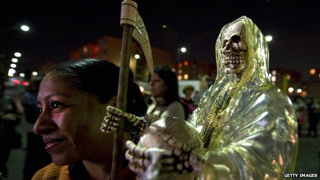A woman holds a statue of Santa Muerte at a procession in Mexico City on 1 November 2012