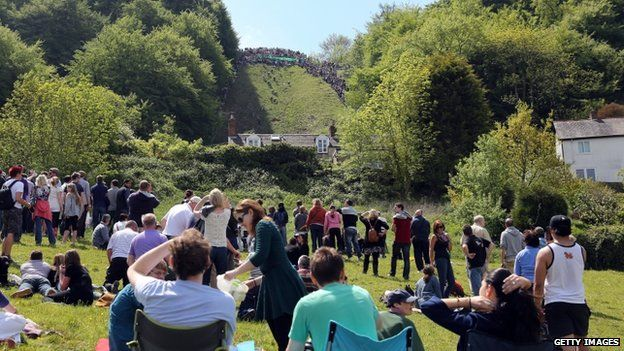 People sit and watch the cheese-rolling races