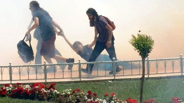 Demonstrators help one another as Turkish riot policemen use tear gas to disperse clashes (May 31, 2013)