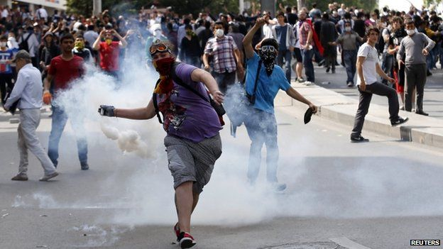A protester throws a gas canister back at riot police during a demonstration in Ankara 3 June 2013