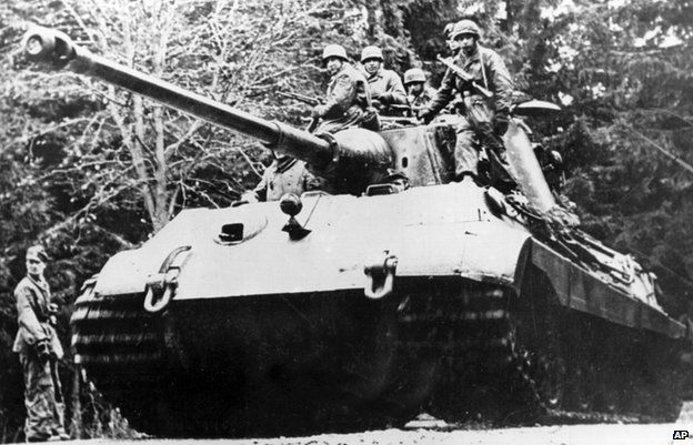 The German Tiger II tank with soldiers sitting on the top