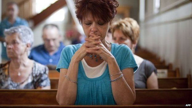 People attend a Mass dedicated to the victims of the train disaster at a church near Lac-Megantic, Canada, 7 July 2013