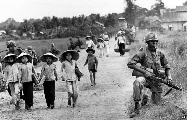US soldier guards Route 7 as Vietnamese women and school children return home