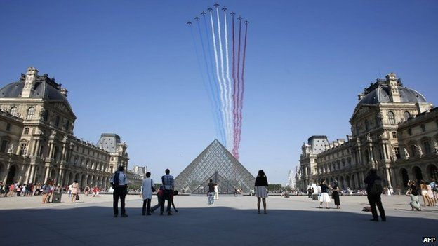Nine jets from the French Air Force Patrouille de France releasing trails of red, white and blue smoke over the Pyramid du Louvre during the Bastille Day parade, 14 July 2013