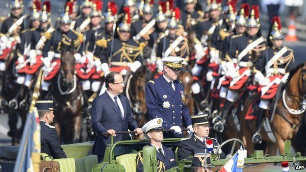 Paris military governor, general Herve Charpentier (r) and French President Francois Hollande review the troops during the Bastille Day parade on the Champs Elysees 14 July