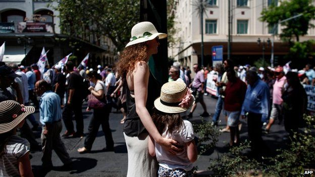 Tourists watch as union members demonstrate in general strike in Athens on 16 July 2013