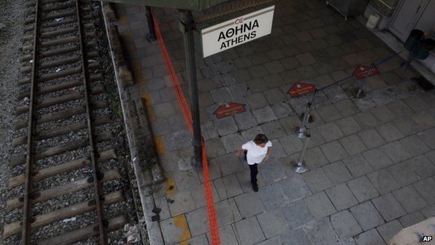 Cleaning worker walks in empty train station in Athens on 16 July 2013