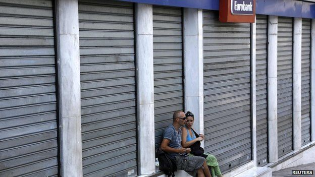 Pedestrians sit in front of closed bank in Athens on 16 July 2013