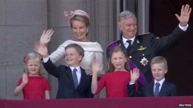 King Philippe, his wife Mathilde and their four children wave to crowds from the balcony of the royal palace in Brussels