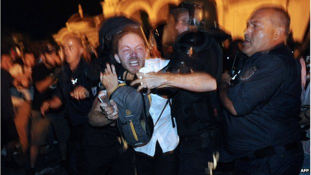 Bulgarian riot policemen push a protestor during an anti-government protest in Sofia on July 23, 2013