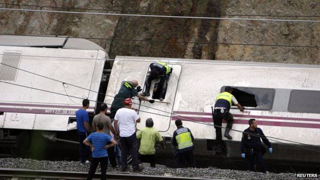 Rescue workers search for victims inside overturned train carriage on 24 July 2013