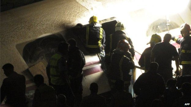 Recue workers search inside of train carriage after train derailed near city of Santiago de Compostela on 24 July 2013
