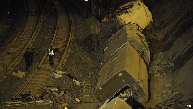 Spanish police officers walk next to derailed cars at site of train accident near Santiago de Compostela on 25 July 2013