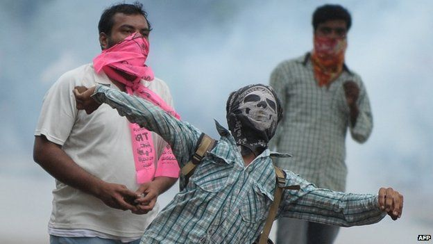 A Telangana Joint Action Committee (T-JAC) activist throws stones towards police during a pro-Telangana protest in Hyderabad on June 14, 2013.