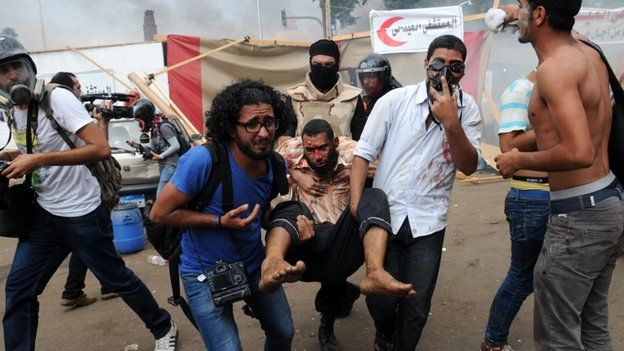 An injured man is carried after security forces break up sit-in at Nahda Square