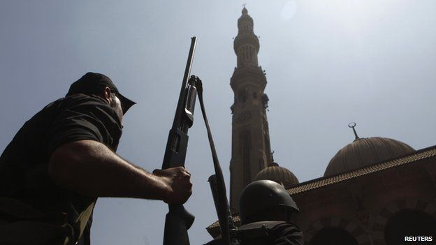 Armed Egyptian policeman moves into position in front of al-Fath mosque on Ramses Square in Cairo (17 August 2013)