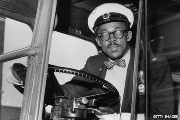A Black London bus driver at the wheel in the late 1950s