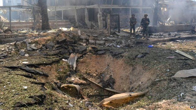 Lebanese army soldiers stand next to crater caused by an explosion outside of a mosque in the northern city of Tripoli, Lebanon, Friday Aug 23, 2013.