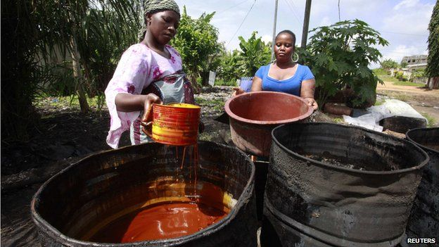 Women prepare to extract red palm oil in Dabou, around 49 km (30 miles) from Abidjan on 12 June 2013