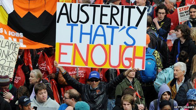 """A man holds a sign saying """"Austerity that's enough"""""""