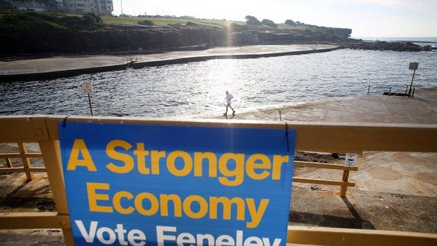 Swimmers exit the water as polls open in Clovelly Beach on 7 September 2013