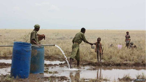 A Kenya police reservist delivers clean water to a thirsty child at the Lotikipi Borehole