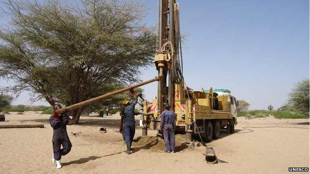 Drilling technicians loading an extra drilling rod to the drilling rig, Turkana, Kenya