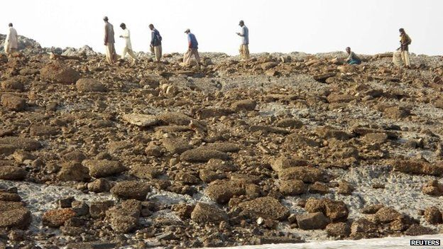 People walk on an island that rose from the sea following an earthquake, off Pakistan's Gwadar coastline in the Arabian Sea 25 September, 2013.