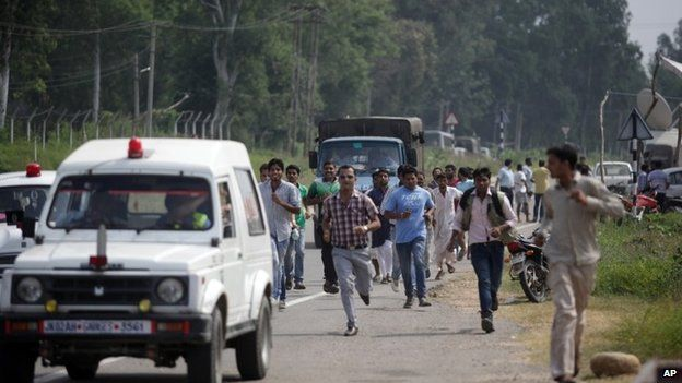 People run beside vehicles as they seek shelter during an attack by militants on an army camp in Samba District