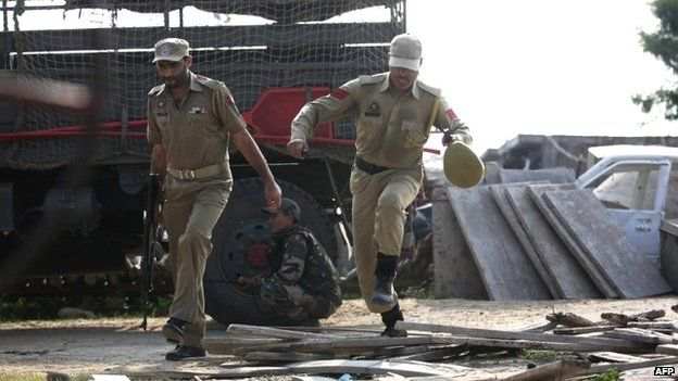 Indian police officials run during an attack by militants on an army camp at Mesar in Samba District
