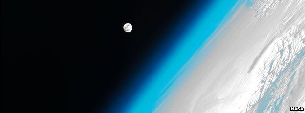 The Moon hovers Earth's atmosphere as seen from the International Space Station