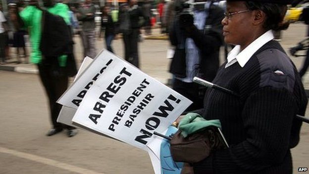 A Kenyan police officer carries confiscated placards in the Kenyan capital, Nairobi, calling for the arrest of Sudan's President Omar al-Bashir on 27 August 2010