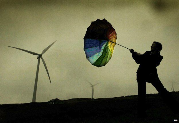 Man with inverted umbrella by wind turbine in storm