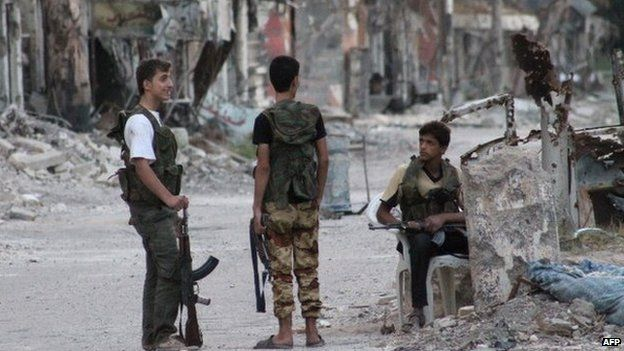 Rebel fighters secure an heavily damaged street in Syria's eastern town of Deir al-Zour on 23 September 2013